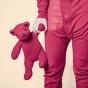 weibliche Hand in rosa Pyjama hält rosa Teddybär