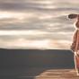Mann in Osterhasenkostüm geht Richtung Sonnenuntergang