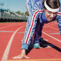 Lady in track suit about to run on a track